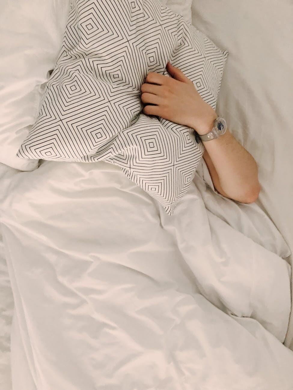 Braccio di persona che spunta da sotto piumino letto